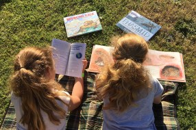 Two primary-aged girls laying on their stomachs on grass reading books.