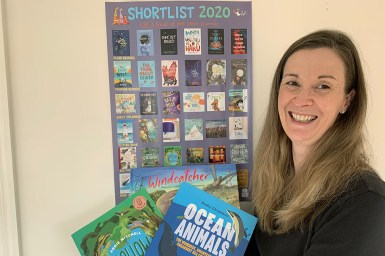 Books Publisher Briana Melideo standing in front of a CBCA 2020 Book of the Year Shortlist poster, holding three CSIRO Publishing children's books