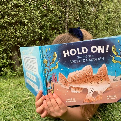 A child reading Hold On picture book with cover shown