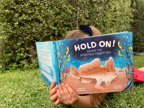 A child laying on grass reading, their face buried in the picture book 'Hold On! Saving the Spotted Handfish'.