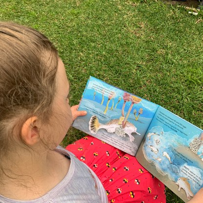 Over the shoulder view of a young girl reading Hold On picture book