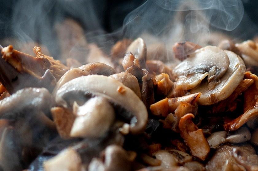 A close up photo of mixed mushrooms cooking