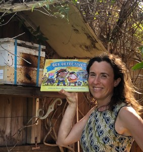 Woman holding a copy of Bee Detectives picture book in front of beehive