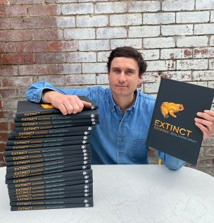 Author Ben Gray seated with a large pile of his book extinct under right arm, and holding a copy to camera in his left.