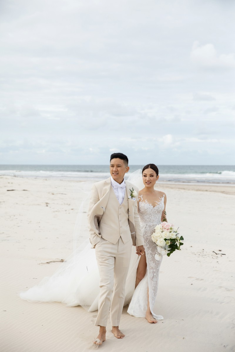 bride-wearing-george-wu-with-groom-walking-on-beach-elements-of-byron-bay-quincenmulberry