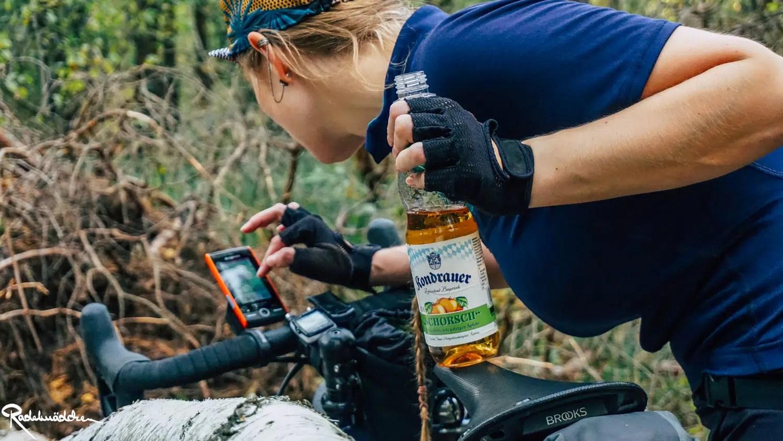 Radelmaedchen übers Fahrrad gebeugt am Navigationsgerät