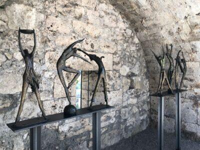 6 Bronzefiguren stehen in einer Arkade