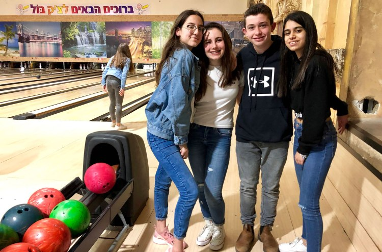 Israeli and American kids bowl together at an Israeli bowling alley.