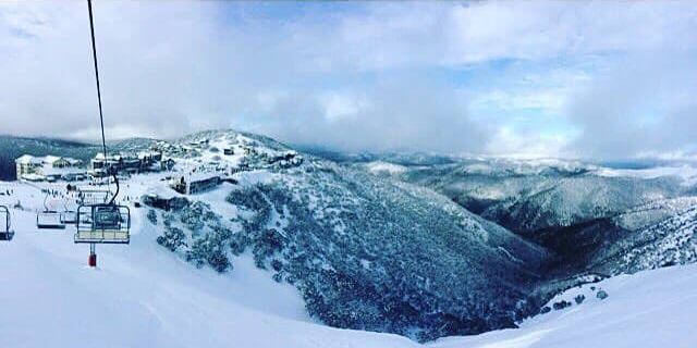 Cloudy day at Hotham ski resort with a valley in the center and an empty chair lift to the left of the photo