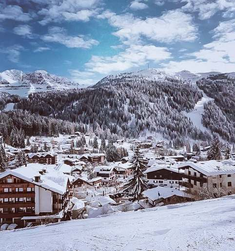 Small snowy town with snowy Italian mountains in the background.