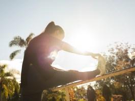 Eine Frau wird von ihrer Rückseite gezeigt. Ihr rechtes Bein streckt sie aus und vollzieht eine Dehnung, in dem sie mit ihrer rechten Hand ihre rechte Fußspitze berührt.