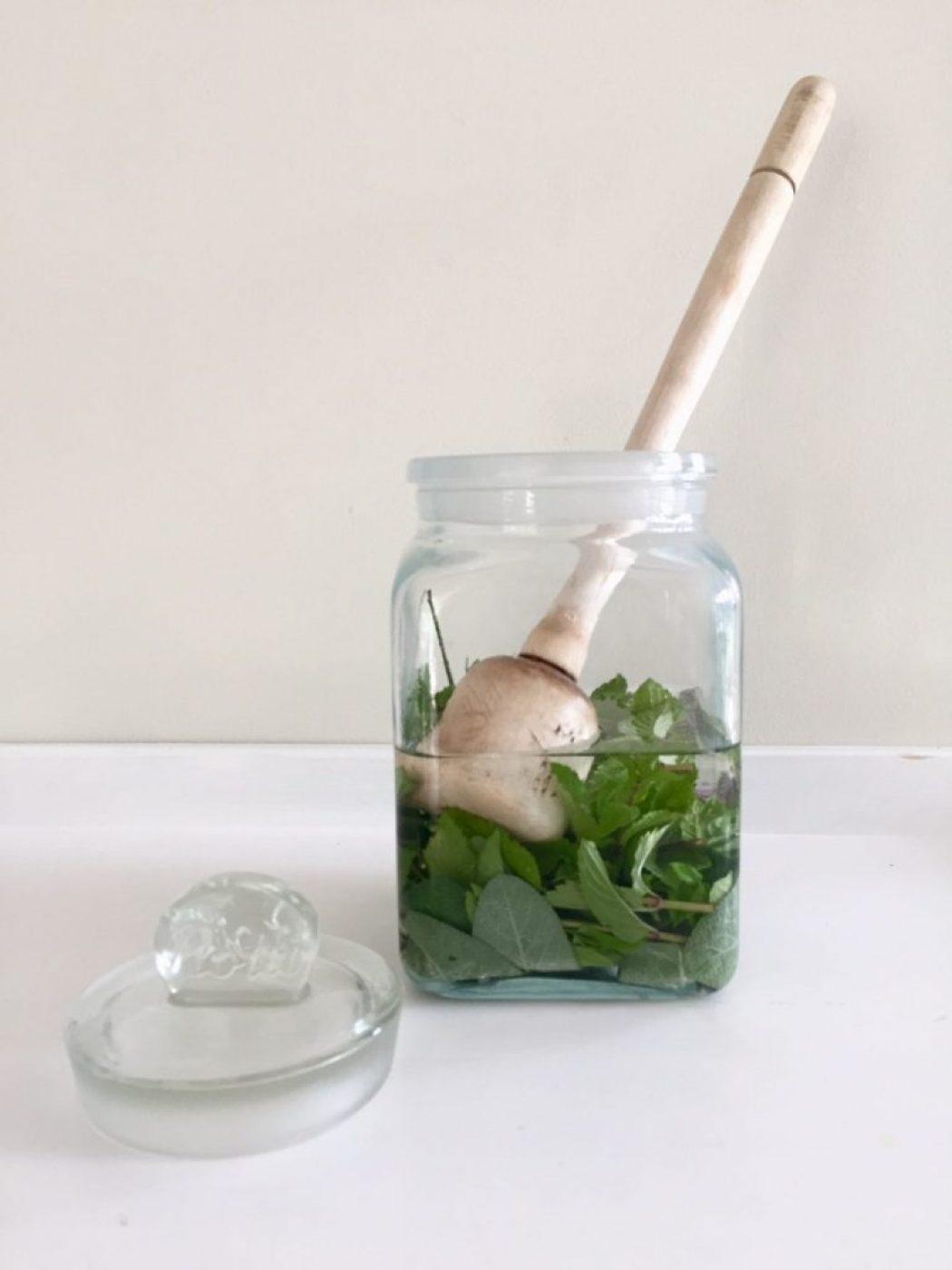 kräuter stampfen in einem glas mit Wodka
