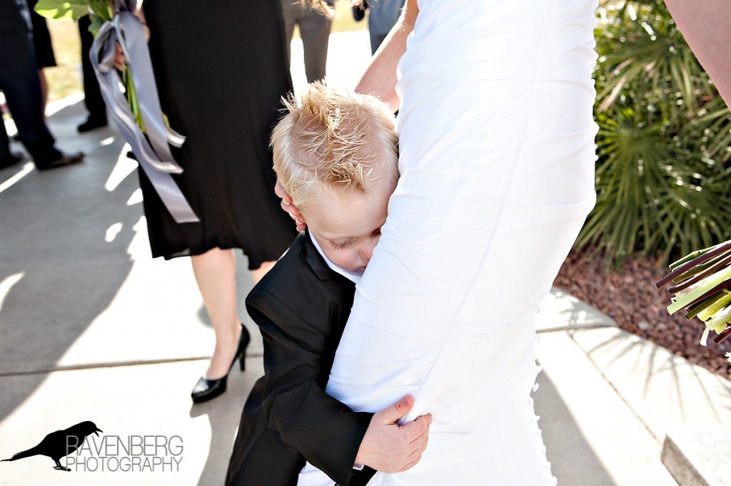 Boy holds onto bride's legs