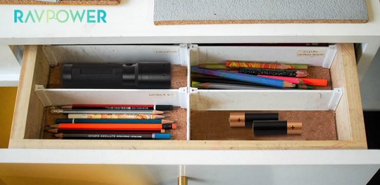 Flashlight batteries pencils crayons inside an open drawer
