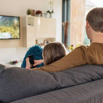 Man sitting on sofa and watching television