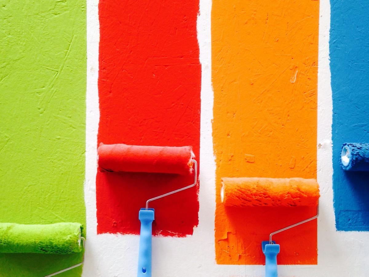 paint rollers making green, red, orange, and blue stripes down a white wall