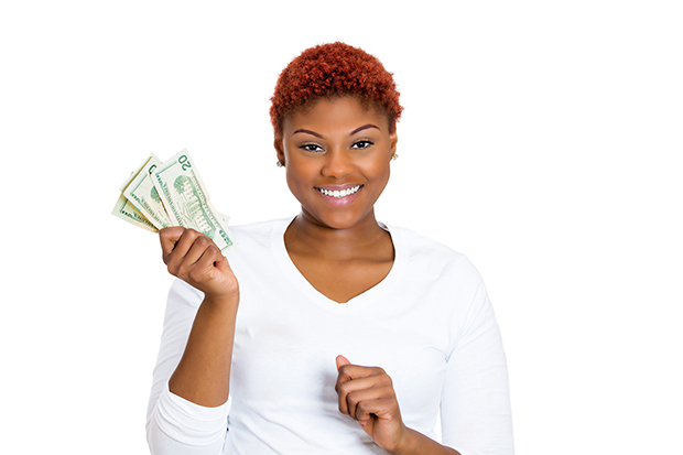 Woman smiling at the camera holding several 20 dollar bills in her hand