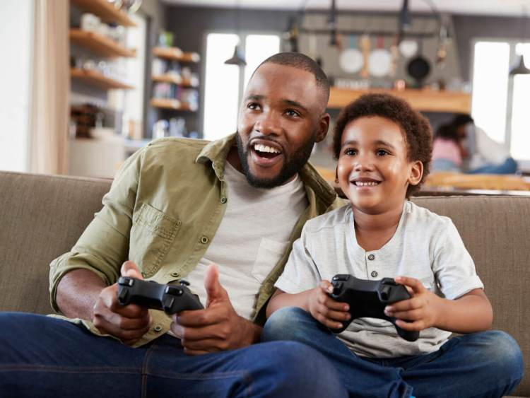 African American father and son on couch playing upcoming PS4 game