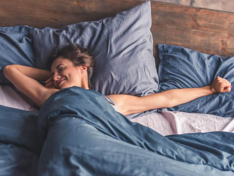 Happy young woman stretching and waking up on new mattress