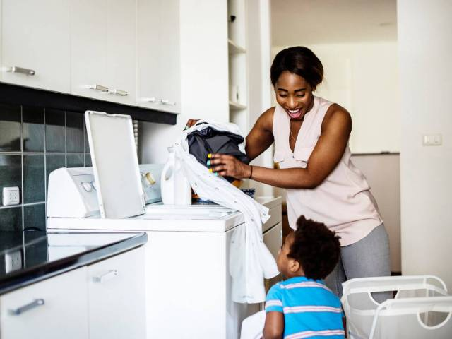 African American mother and son loading washer and dryer with laundry