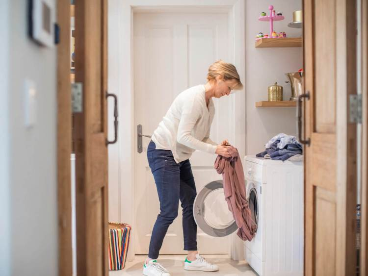Woman puling clothes out of front load washer or dryer
