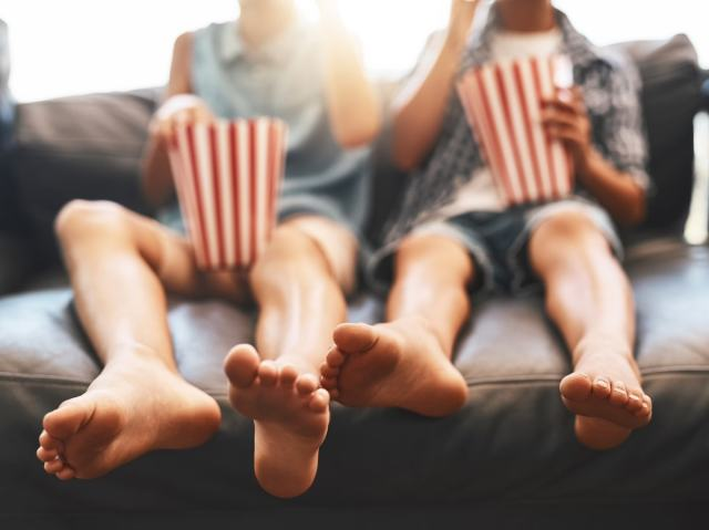 man and woman sitting next to each other on sectional while eating popcorn