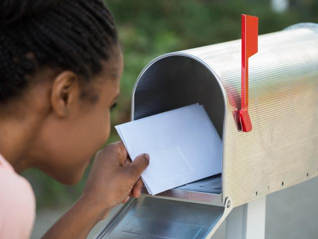 Woman getting mail out of new silver mailbox with red flag up