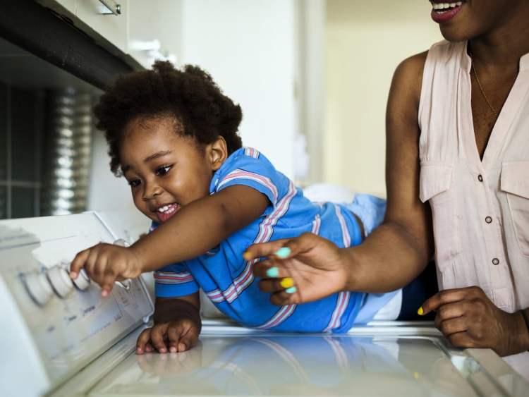 Daughter helping turn on the washing machine