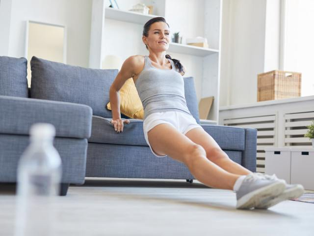 Woman doing tricep pushup on couch
