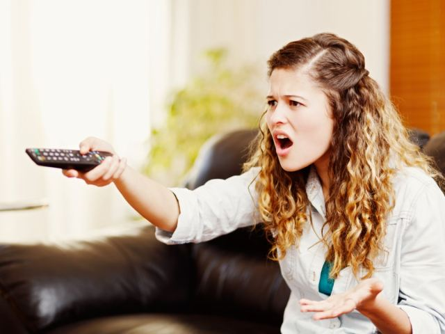 Upset woman pointing remote at TV