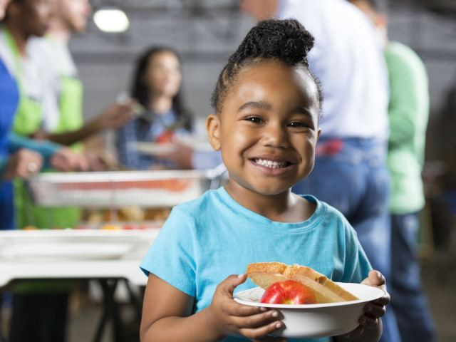 Girl holding a plate of food at a food bank