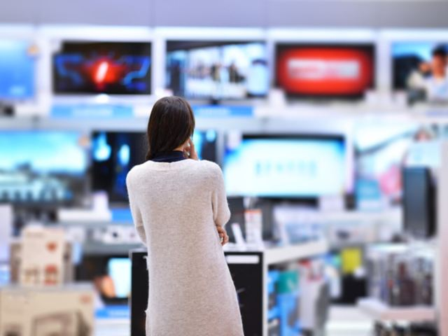 Woman contemplating over a new TV in an electronics store