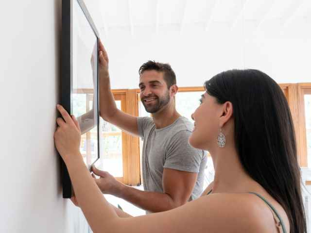 smiling couple hanging picture frame in home