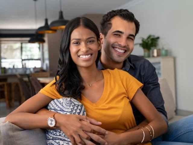 Smiling couple sitting on sofa facing camera