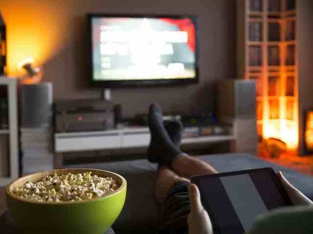 Person wearing black socks watching television while holding tablet with a green bowl of popcorn.