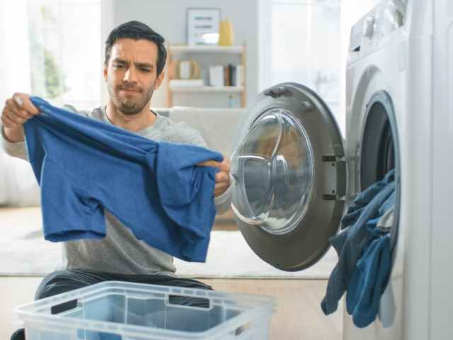 Man removing clothing from dryer with frustrated expression.