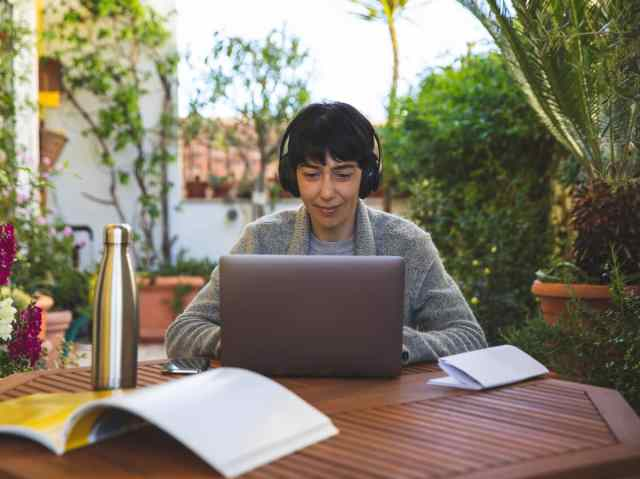 Woman on patio with headphones on working on laptop.