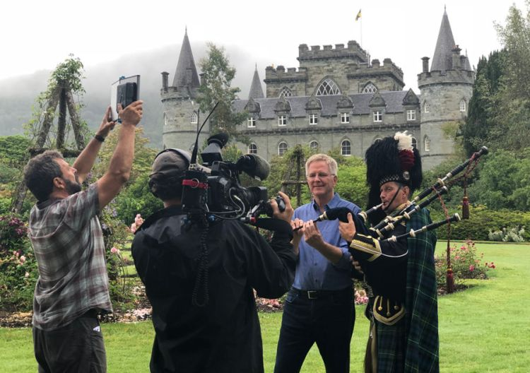 rick steves with a scottish piper being filmed by a tv crew in front of a large camera