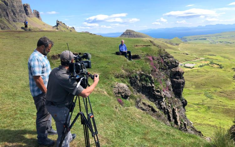 rick steves sitting on the edge of a cliff and the tv crew pointing a camera at him in the foreground