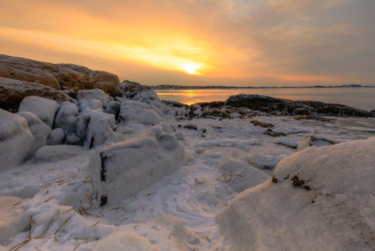 Sunset over frozen rocks at Annisquam Lighthouse