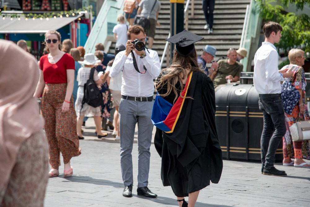 A man photographs a graduate