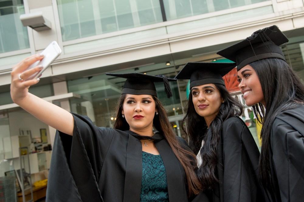 Three graduates take a photo together