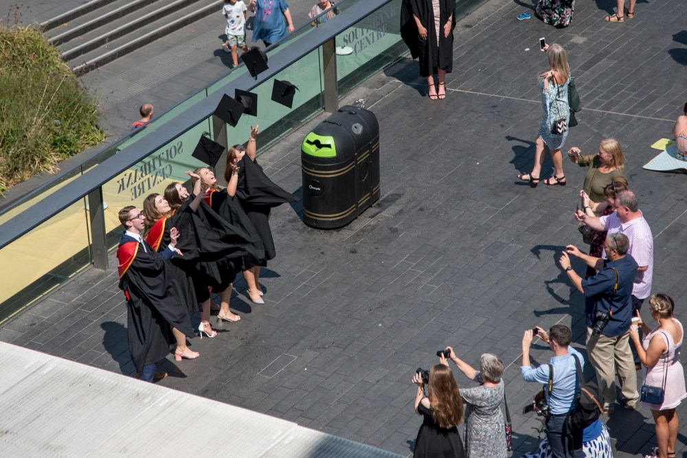 Several students throw their mortarboards, as a bin watches, enviously, the regret that it didn't enrol at the University of Roehampton palpable.