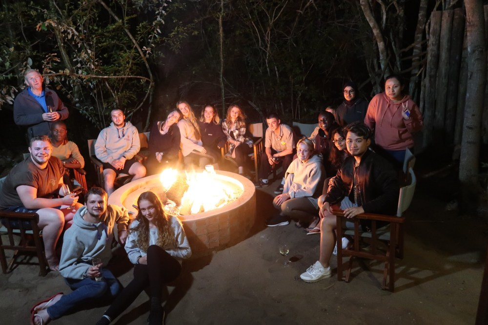Roehampton students gathered round a campfire