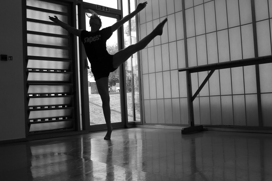 A black and white photo of a student dancing in a dance studio