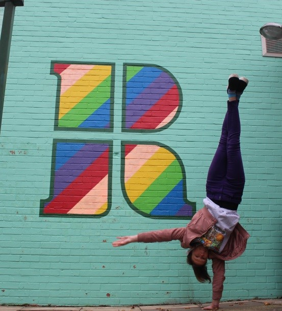 A student doing a handstand by the 'Rainbow R' mural