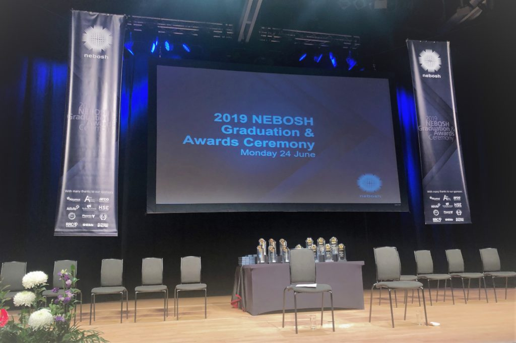 Image of the stage, with 2019 NEBOSH Graduation & Awards Ceremony on a screen