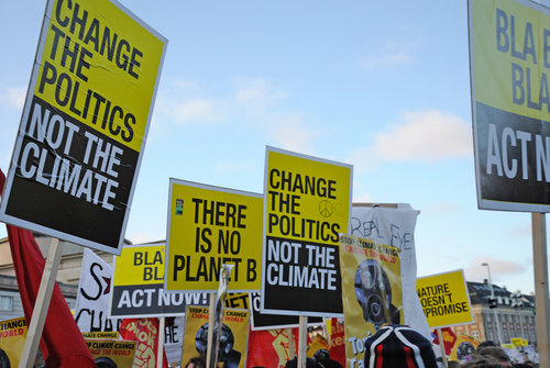 Image of posters from an environmental protest - reading 'change politics not the climate'