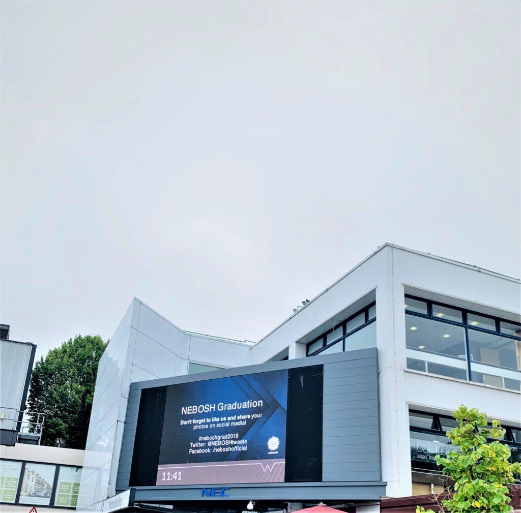 Warwick University with an interactive screen reading NEBOSH Graduation...