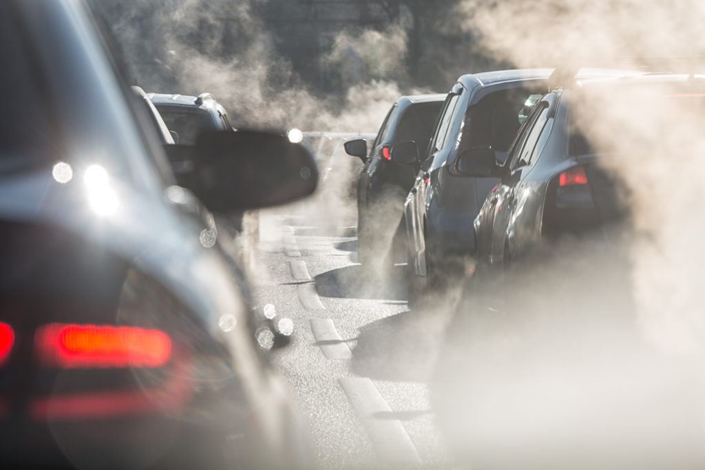Cars in traffic in the city with visible emissions